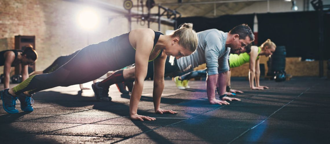 66780729 - group of adults doing push up exercises at indoor physical fitness cross-training exercise facility with bright light flare over them